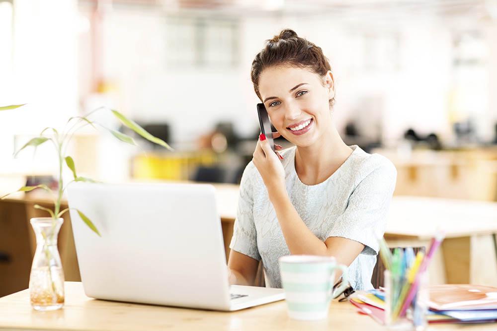Portrait of smiling female entrepreneur answering smart phone while using laptop at desk in office. Horizontal shot.